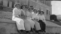 Image of Women on wall in front of library, 1911