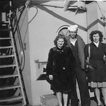 Image of Two sailors and two women standing on deck of battleship. - 2008.047.087