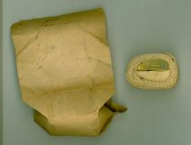 Image of Civil War field tourniquet, cloth webbing with brass buckle. Brown paper wrapping.  - 2001.0703