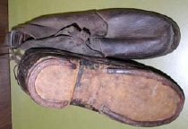 Image of Confederate Army shoe.  (left) Leather uppers, wooden soles, horseshoe-like metal cleats, metal snaps - 2001.0703