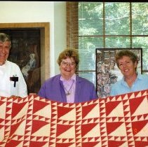 """Image of Quilt - Quilt, 89"""" x 92"""" approx, red & white cotton in sawtooth & triangles pattern, hand stitched & quilted.  Handwritten names of approx 500 members of the Ladies' Benevolent Society and notation """"Presented to Mrs. Cyrus Page by the Ladies' Benevolent Society, Bedford, 1882.  Minor staining, fading."""