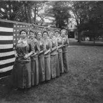 """Image of Print, Photographic - Photograph showing 7 ladies standing in a row in front of large flag; barn in background. Wearing ribbons that say """"Bedford Old Home Week"""" (which was held in 1912). Third from left is Ruth Comley Webber. May be members of the Order of the Eastern Star? To judge by the fence and the expanse of grass, the setting is Bedford Common. The barn in the background is likely to be the one that belonged to the Bedford House hotel."""