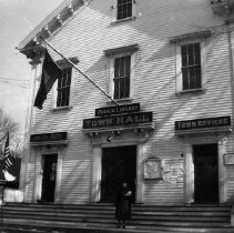 """Image of Print, Photographic - Modern print of old photograph showing Old Town Hall (16 South Road) with woman standing on steps. With negative of same. Written on back by John Brown: """"Town Hall in Bedford, Mass., Oct. 1942. The woman might be Leona Cail, librarian. The #177 [on flag, not visible in this shot; can be seen in 2004.022.11] is the number of servicemen from Bedford."""""""