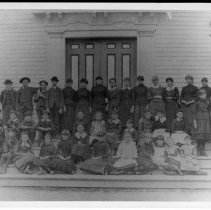 """Image of Print, Photographic - Modern reprint of group photo, schoolchildren and teachers on steps of Old Town Hall, 1886. All identified on back of photo. Seems to be another shot of group shown in P1976.24.2b.   Written on back:   """"Photo by Chas. O. Hodgeman [sic] -- 1886. Left to right.  """"Standing: Louise Whicher (teacher), Eugene Laws, Frank Cary, Chas. Kenrick, Win Fitch, Lizzie Webber, Annie McGovern, Katie Nevill, Alice Johnson, Alice Fitch, Edith Hartwell, Fannie Piper, Jennie Cutler, Lottie Cory, Mallie Lawrence, Miss Merriman (teacher).  """"2nd row - (seated): Gorham Pearson, Ernest Lane, Fred Laws, Henry Nevill, Mary Conners, May Wood, Bertha Ramsdell, Lenore Flint, Lena Hunter, Mary Haynes, Maggie Kelley. (standing): Fannie L. Wood, Alice Ramsdell.  """"3rd row: Howard Wood, Will Kane, John Blake, Delia Kelley, Florence Skilton, Olive Webber, Jennie Murray, Fannie A. Wood, Rachel Ford, Grace Russell, Edie Blake, Ada Corey, Mary Dutton."""""""