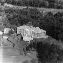 Image of Print, Photographic - Aerial photo of a portion of the Marist Seminary.  Buildings, left to right, as identified by donor: nuns' house (still standing); nuns' house (later burned down); Marist education building (a.k.a. Marist Ed, still standing). In front of education building, priests' house. Small structure in front of nuns' houses was an arbor. Route 3 can be seen in background. Tennis courts on far right of picture no longer exist, nor does baseball diamond in left foreground. All now part of the Middlesex Community College grounds.