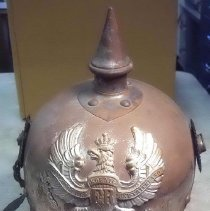 """Image of Helmet - German """"pickelhauben"""" (spiked helmet), steel. On front, imperial eagle bearing banner that reads, """"Mit Gott für Koenig un Vaterland"""" (with God for king and fatherland). Stamped on inside, """"C. E. Juncker 1916."""" With linen cover made to fit over spike; """"L 65"""" in green applique on front of cover."""