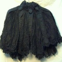 Image of Cape - Woman's cape, 1895. Black shoulder cape. Strips of black satin with beads sewn on elegant lace cape, all radiating from pleated silk neck with short radiating bead trimmed short satin tabs.