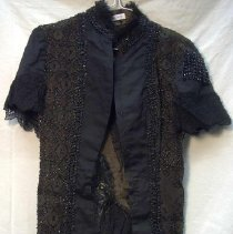 Image of Cape - Woman's little shoulder cape. Black faille or ribbed silk with black beaded trim and hook and eye closure. Long front panels ending in bead fringe. V-shaped rear panel ending in lace flounce with silk bow. Heavy beaded fringe missing from one shoulder. Nancy Rexford, clothing consultant, said that this garment should be KEPT.