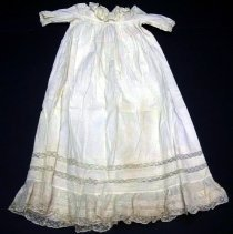 Image of Dress - Long white cotton infant dress, rounded yoke with lace insets and tiny tucks. Machine stitching. Two bands of inset lace, 5 bands tiny tucks, lace edging at bottom.