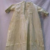 Image of Dress - Infant dress, 1 meter long. Cotton, fine muslin, with greenish cast. Square eyelet and tucking on yoke, pleated front. 13.5 cm tucking, 12 cm eyelet ruffle at hem. Lace neckline, tucking eyelet and lace on sleeves. 4 button back closure.