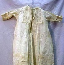 Image of Gown, Baptismal - Infant's christening gown. 106 cm. White muslin. Drawstring square neck. Tucked and eyelet back and front yokes. At bottom, tucked band with eyelet insert 14 cm. Eyelet ruffle 13 cm. Sleeves with tucking and lace.