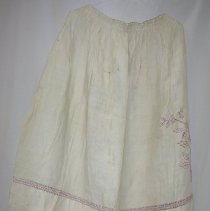 Image of Apron - Woman's apron. Heavy white linen with red embroidered floral spray and red-trimmed drawn work band. 10 cm with knotted work (lace? trim. Nancy Rexford, clothing expert, said that this is an important garment and should be kept.)