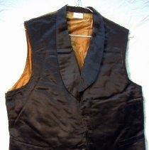 Image of Waistcoat - Man's waistcoat, black in front and brown in back, single breasted, seven small buttons (one detached and stored in breast pocket) , one breast pocket and two hip pockets, lined with white fabric. Metal buckle on back belt. No tailor's label.  Inner facing includes a small piece of brocade and strips of leather along bottom edge.