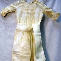Image of Gown, Baptismal - Baby's white christening dress. Round neckline with square yoke. Lace at neck, sleeves, and hem. Two sets of eight tiny tucks above lace on hem. Back placket closed with two buttons. Wide white sash.