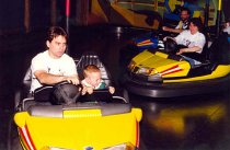 Image of PA and baby riding bumper cars, 1997
