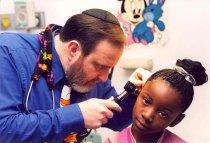Image of Israel Bochner examining patient's ear