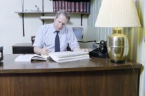 Image of SIC00368 - Ken Ferrell looking over insurance records at his desk in his office at Duke University