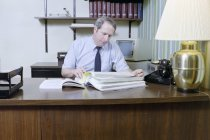 Image of SIC00369 - Ken Ferrell looking over insurance records at his desk in his office at Duke University