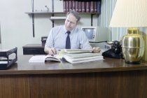 Image of SIC00370 - Ken Ferrell looking over insurance records at his desk in his office at Duke University