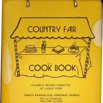 Image of Country Fair Cook Book - This item is a cookbook compiled by the ladies from Trinity Evangelical Covenant Church in 1974.  The cover is yellow and contains the image of a table.