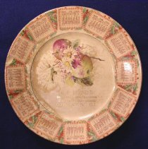 Image of Behrend's Hardware Commemorative Plate - This item is a commemorative calendar plate produced for Behrend's Hardware Store in 1909.  The front has an image of flowers and fruit along with a calendar running clockwise along the edge.