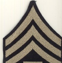 Image of United States Army Rank Insignia Uniform Patch - This item is a United States Army Staff Sergeant uniform patch from World War II.  The patch is black and gold with the letter T in the center.  It was owned by Harold Lawson, a former area resident who served in the armed forces.