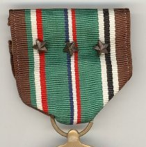 Image of World War II Campaign Medal - This item is a campaign medal awarded to Oak Lawn resident Cathel Munro for his service in World War II. There is an image of an eagle as well as troops landing on a beach. Also included are one single campaign ribbon, as well as one campaign ribbon attached to a Defense Service Ribbon. Munro served with the 9th Infantry in the European theatre of war.