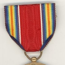 """Image of World War II Victory Medal - This item is a World War II Victory Medal awarded to Oak lawn resident Cathel Munro for his service in the conflict.  There is an image of the Roman God Nike standing victorious and a listing of the """"Four Freedoms"""" on the back.  Munro served with the 9th Infantry in the European theatre of war."""