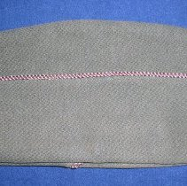 Image of Harold Lawson WWII Army Uniform Dress Cap - This item is a United States Army uniform cap from World War II.  It is olive green with dark red and white trim running down the side.  The cap was owned by Harold Lawson, a former area resident who served in the armed forces.