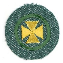 Image of Girl Scout Health Aid Merit Badge - This item is a Girl Scout Health Aid merit badge owned by local resident Marilyn (Drozdz) Brand.  It is green in color with a yellow symbol near its center.