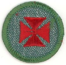 Image of Girl Scout First Aid Merit Badge - This item is a Girl Scout First Aid merit badge owned by local resident Marilyn (Drozdz) Brand.  It is green in color with a red symbol near its center.