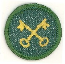 Image of Girl Scout Housekeeper Merit Badge - This item is a Girl Scout Housekeeper merit badge owned by local resident Marilyn (Drozdz) Brand.  It is green in color with an image of keys near its center.