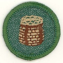 Image of Girl Scout Campcraft Merit Badge - This item is a Girl Scout Campcraft merit badge owned by local resident Marilyn (Drozdz) Brand.  It is green in color with an image of a basket near its center.