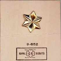 Image of Girl Scout Membership Pin - This item is a Girl Scout membership pin from the 1950s.  It is in the shape of a star, gold in color, and was owned by local resident Marilyn Brand.