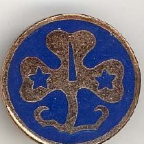 Image of Girl Scout WAGGGS Pin - This item is a Girl Scout WAGGGS (World Association of Girl Guides and Girl Scouts) pin from the 1950s.  It is circular in shape while gold and blue in color.  The pin was owned by local resident Marilyn Brand.