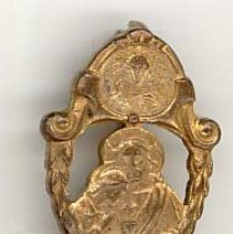 Image of St. Gerald First Communion Pin - This item is a St. Gerald School First Communion pin from the 1950s.  It is gold in color and has an image of Jesus and Mary near the center. The pin was owned by local resident Marilyn Brand.