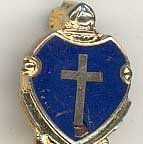 Image of St. Gerald Pin - This item is a St. Gerald School pin from the 1950s.  It is gold and blue in color with the image of a cross near the center. The pin was owned by local resident Marilyn Brand.