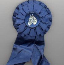 Image of Oak Lawn Round-Up Ribbon, 1955 - This item is a blue ribbon given out during the 1955 Oak Lawn Round-Up.  There is an image of a horse in the ribbon's center and text on the lower half.