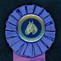Image of Oak Lawn Round-Up Ribbon, 1954 - This item is a purple ribbon given out during the 1954 Oak Lawn Round-Up.  There is an image of a horse in the ribbon's center and text on the lower half.