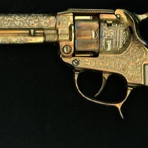 Image of Oak Lawn Round-Up Toy Gun - This item is a toy gun used during the Oak Lawn Round-Up Days.  The gun is gold in color, has a white handle, and comes with a leather holster.  It would have been worn during programs, parades, and other events.