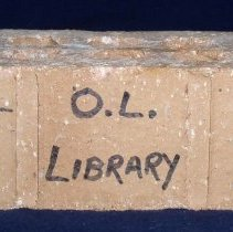 Image of Brick from Oak Lawn Public Library - This item is a brick from the Oak Lawn Public Library building completed in 1955. It has writing in marker on the side, and is red in color.  This Library structure, which replaced the Chamberlain Home, would serve the public for many years.  It was torn down in 2002 to make way for a new addition.