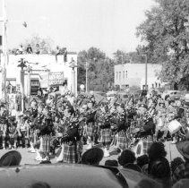 Image of Oak Lawn Round-Up Days Parade - This is a photograph of the Oak Lawn Round-Up Days parade on 95th Street near Cook Avenue. Structures such as the Sinclair Service Station (left) and Fire Department (right) can be seen in the background.