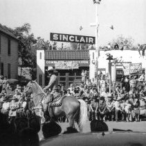 Image of Oak Lawn Round-Up Days Parade - This is a photograph of the Oak Lawn Round-Up Days parade on 95th Street near Cook Avenue. Structures such as the Hilgendorf House (left) and Sinclair Service Station (right) can be seen in the background.
