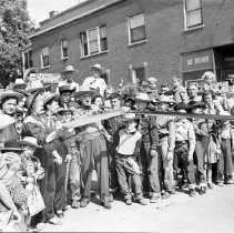 Image of Oak Lawn Round-Up Days Ribbon Cutting - This item is a negative of the ribbon cutting ceremony at the Oak Lawn Round-Up Days.  Mayor Harvey Wick cut the ribbon for the afternoon festivities, and in the center holding the pistol is Al Schnitz, Director of the Chamber of Commerce.  Nick's (Schultz) Tavern can be seen in the background.