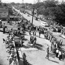 Image of Oak Lawn Round-Up Days Parade - This item is a negative of the Oak Lawn Round-Up Days Parade on 95th Street.  Numerous spectators can be seen on either side of the road, and the Oak Lawn Water Tower is visible in the distance.  It was estimated that 75,000 people turned out to see the parade that year.