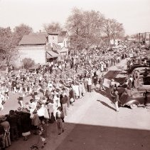 Image of Oak Lawn Round-Up Days Parade - This item is a negative of the Oak Lawn Round-Up Days Parade on 95th Street near Cook Avenue. Numerous spectators and automobiles can be seen lining the road.
