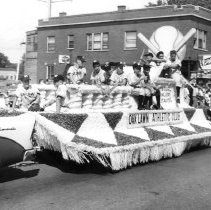 Image of Oak Lawn Round-Up Days - This is a photograph of the Oak Lawn Round-Up Days parade down 95th Street.  The float is sponsored by the Oak Lawn Athletic Club, with members of the baseball team riding on top.  Roger Chimino can be seen fourth from the left, and Nick's (Schultz) Tavern is visible in the background.