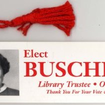 Image of Joann Buschbach Promotional Bookmark - This item is a promotional bookmark distributed by Joann Buschbach while running for the position of library trustee. It is red and white in color with text and images on both the front and back.