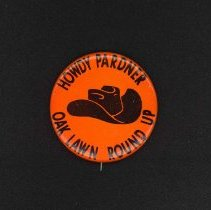 Image of Oak Lawn Round-Up Button - This item is a pin from the Oak Lawn Round-Up. It is orange in color with black lettering and features the image of a cowboy hat near the center. Held from 1949-1958, the Round-Up was a western themed celebration that included a parade, rides, and other events.
