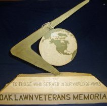 Image of Design Model for Proposed Oak Lawn Veteran's Memorial - This item is a design model for the proposed Oak Lawn Veteran's Memorial. It was built by Marvin H. Boulter, an area resident, commercial artist, and World War II veteran. The model was completed between 1989 and 1990, although it was not chosen as the winning design. The Veteran's Memorial was completed and dedicated in the Fall of 1996.